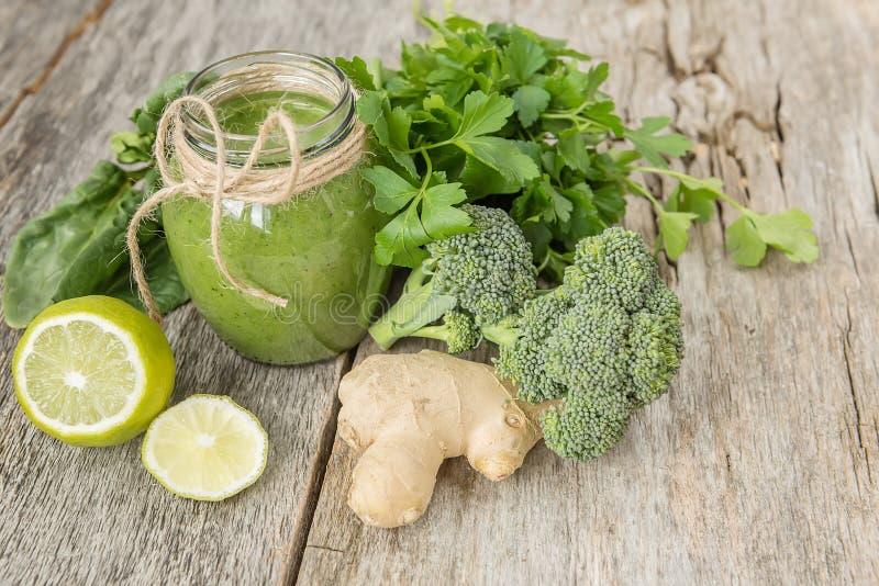 Smoothies av gröna grönsaker och olika gröna grönsaker omkring på en gammal träsprucken bakgrund Coctailen av vitaminer gör ren royaltyfria foton