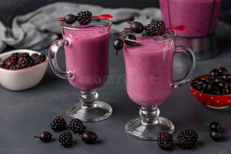 Smoothies with blackberries and gooseberry in glass on a dark background, horizontal photo. Close-up royalty free stock image