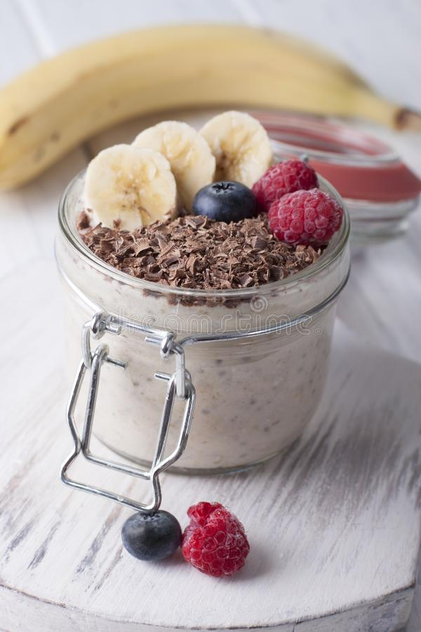 Smoothies with chia seeds, oatmeal, banana and berries of blueberries, raspberries and grated chocolate royalty free stock photos