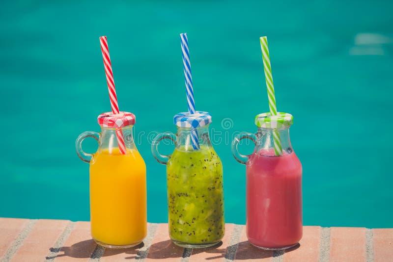 Smoothies coloridos frescos del zumo de fruta en el borde del poo de la natación imagen de archivo