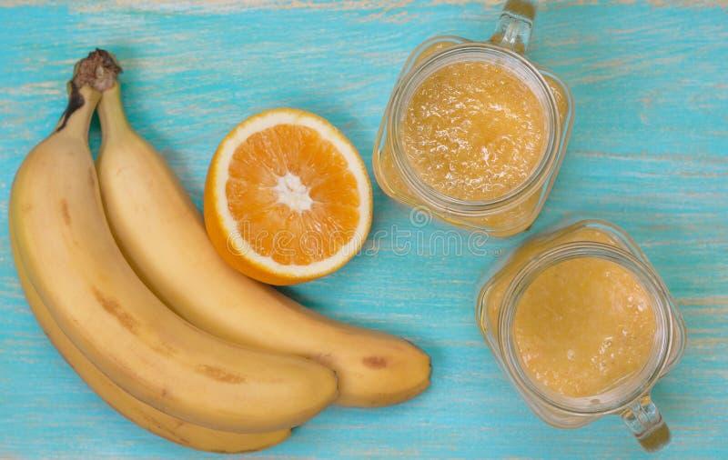 Smoothies con la naranja y el plátano (visión superior, foco selectivo) imagenes de archivo