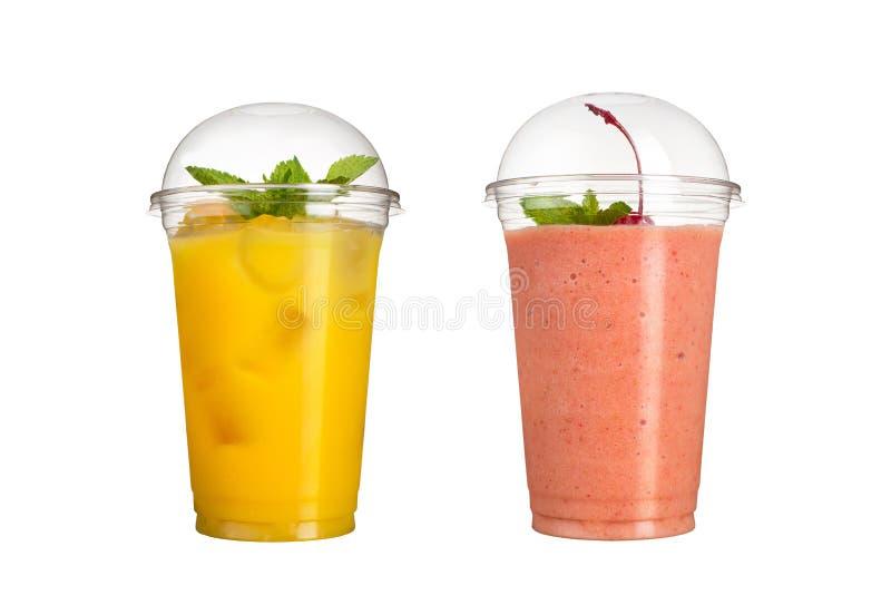 Smoothies délicieux de fruit dans des tasses en plastique, sur un fond blanc Deux cocktails avec un goût d'ananas et de cerise image libre de droits