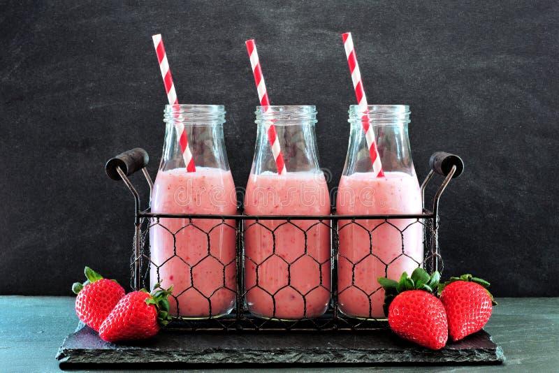 Smoothies de la fresa en botellas en una cesta de alambre del vintage sobre pizarra oscura foto de archivo libre de regalías