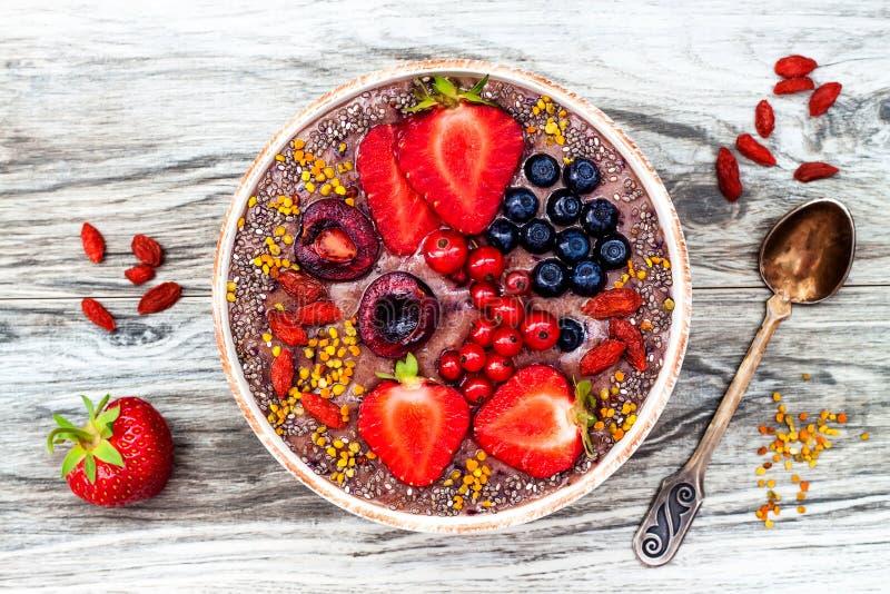 Smoothies för Acai frukostsuperfoods bowlar med chiafrö, bipollen, gojibärtoppningar och jordnötsmör overhead royaltyfria foton