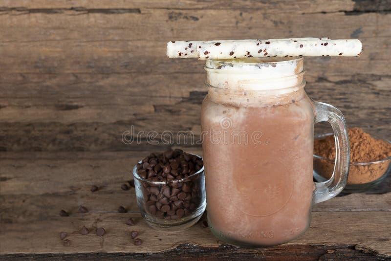 Smoothies för bananblandningchoklad mjölkar satte ett exponeringsglas på en träbakgrund arkivbild