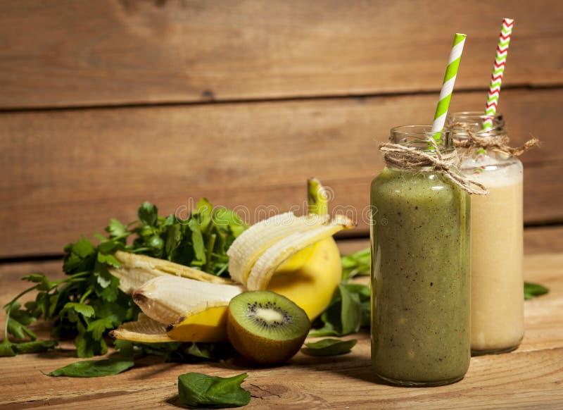 Smoothies fraîchement mélangés de vert et de banane dans des bouteilles en verre avec des pailles photos stock