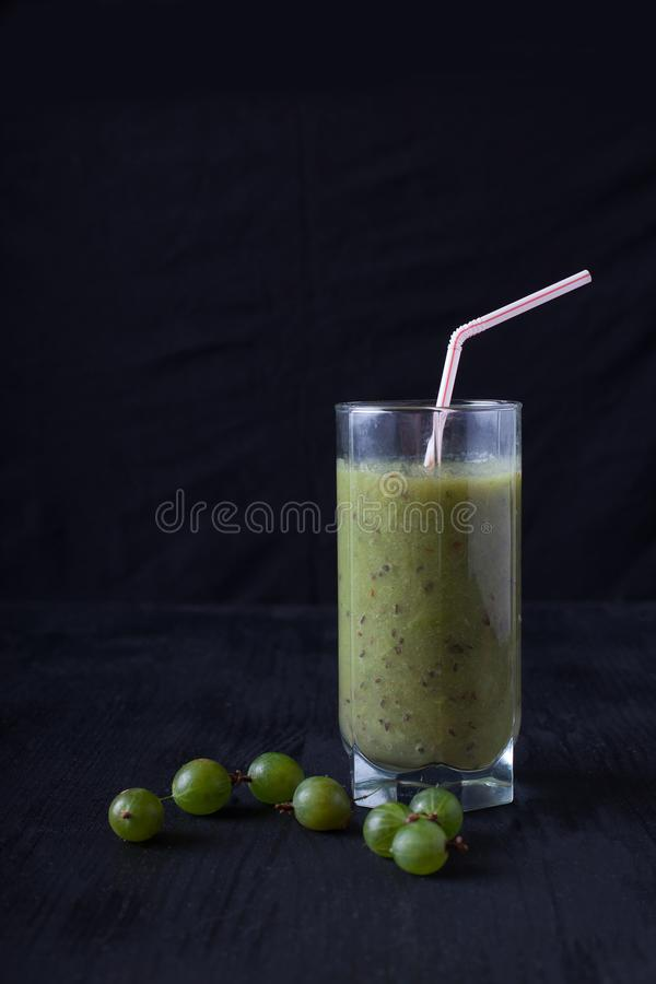Fresh smoothies from gooseberry in a glass of styot on a black t. Smoothies from gooseberry in a glass of styot on a black table stock photography