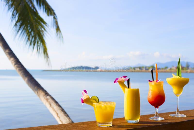 Smoothies i koktajli/lów mangowi napoje z słomą i mennicą w szklanej zlewce Tropikalna owoc na Drewnianym biurku i tropikalny zdjęcie royalty free