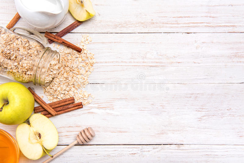 Smoothies with oatmeal, apple and cinnamon in glass jars on a wooden background. royalty free stock images