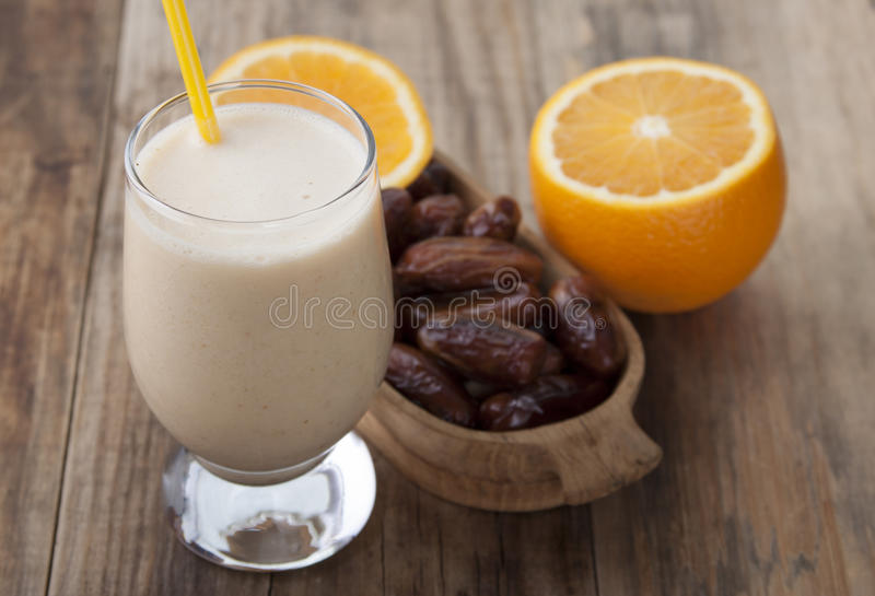 Smoothies of orange and dates . Smoothies of orange and dates with yogurt in a glass on a wooden table stock photos