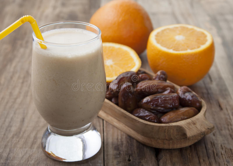 Smoothies of orange and dates . Smoothies of orange and dates with yogurt in a glass on a wooden table stock image