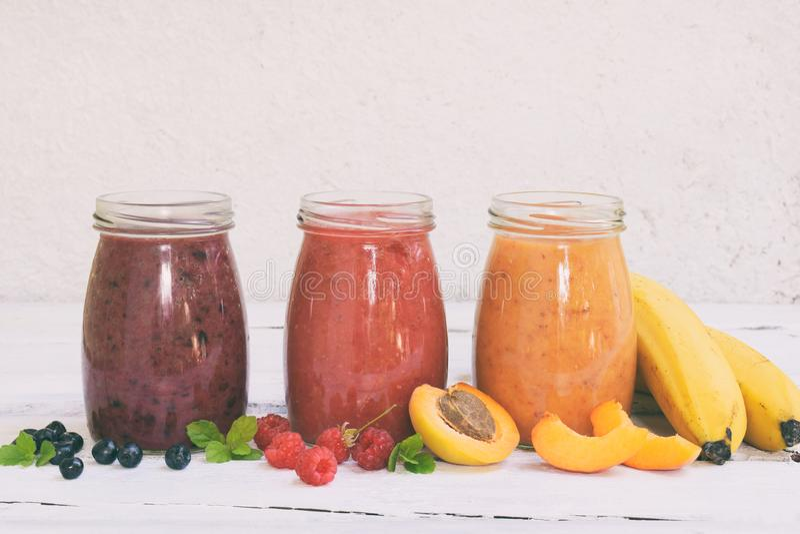 Smoothies oranges, rouges et pourpres des ingrédients frais - bananes, abricots, framboises et myrtilles sur un fond clair guéris image stock