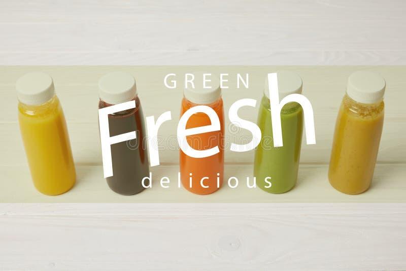 smoothies organiques frais dans des bouteilles se tenant dans la rangée sur le blanc, inscription délicieuse fraîche verte images libres de droits