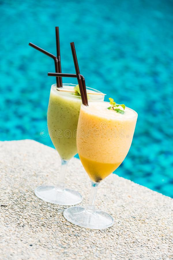Smoothies with pool background. Iced fruit smoothies with pool background royalty free stock image