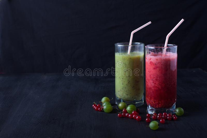 Smoothies of red currants and gooseberries stand on a on a black. Fresh smoothies and gooseberries in a glass stands on on a black wooden table royalty free stock photo