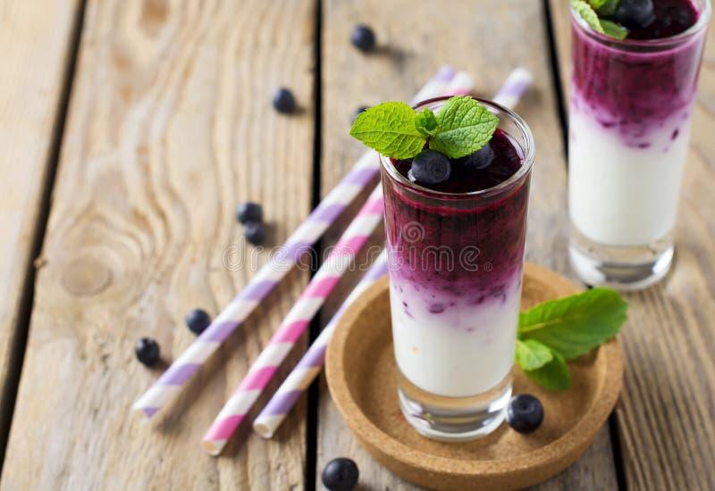 Smoothies sains frais de myrtille dans un verre avec des baies et des feuilles en bon état sur un support en bois photo libre de droits