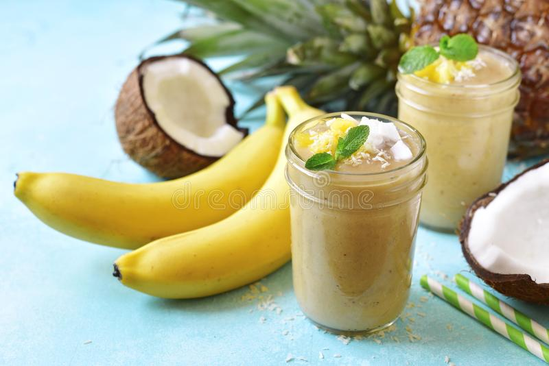 Smoothies tropicaux avec banan, noix de coco et ananas images stock