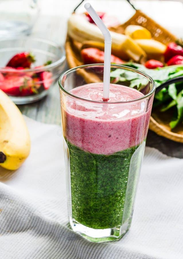 Smoothies, verdes dobles con espinaca y el plátano con el strawberrie imagen de archivo