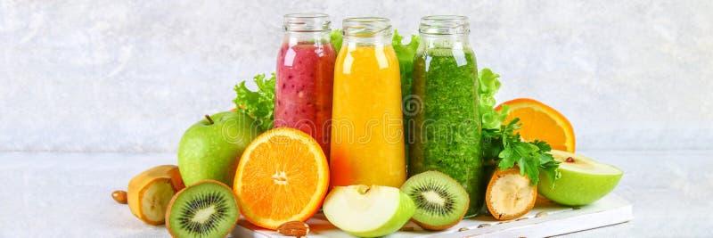 Smoothies verts, jaunes, pourpres dans des bouteilles de groseille, persil, pomme, kiwi, orange sur une table grise photo stock