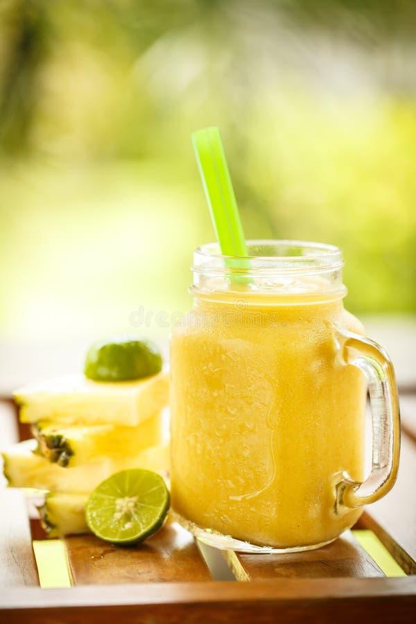 Smoothiesananas med limefrukt i krus royaltyfria bilder