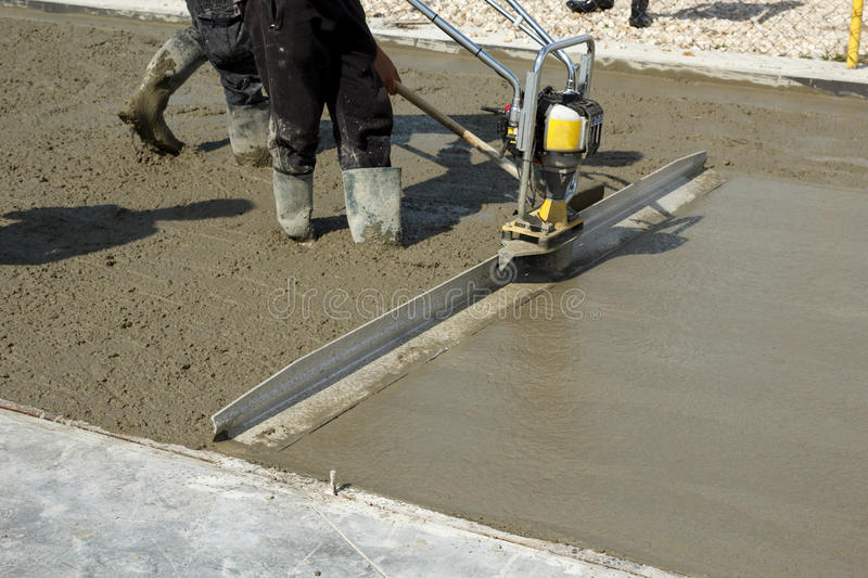 Smoothing concrete with gas powered vibrating screed for Regle construction piscine