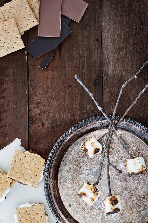 Smores and Ingredients. Over a rustic wooden background royalty free stock photo