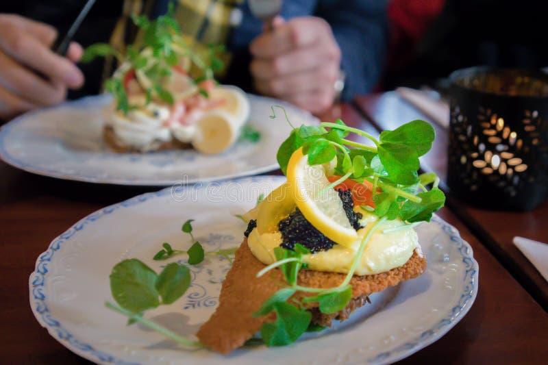 Smorrebrod aperto danese tradizionale dei sanwiches con il pane di segale scuro, il pesce fritto, il caviale nero, il limone ed i fotografia stock