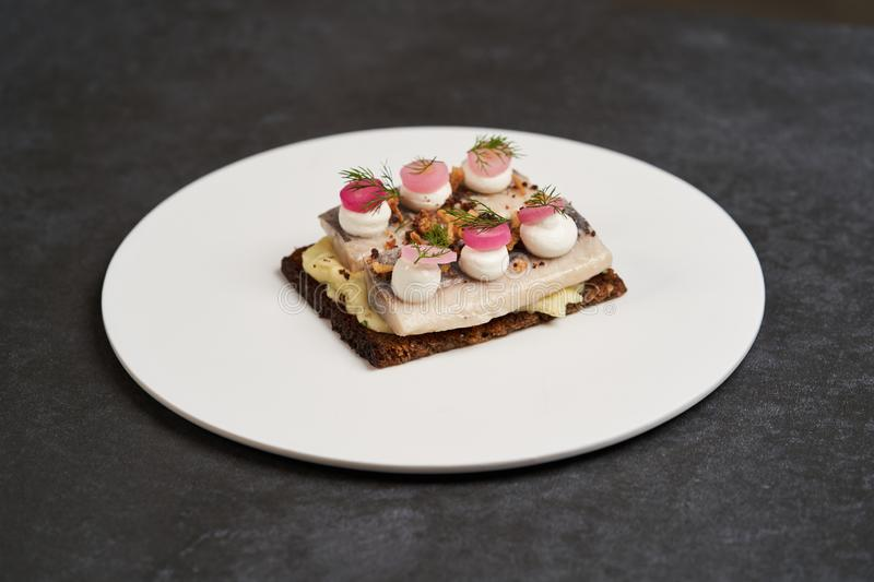 Smorrebrod with Baltic herring fish, smoked mousse and pickled onions stock photography
