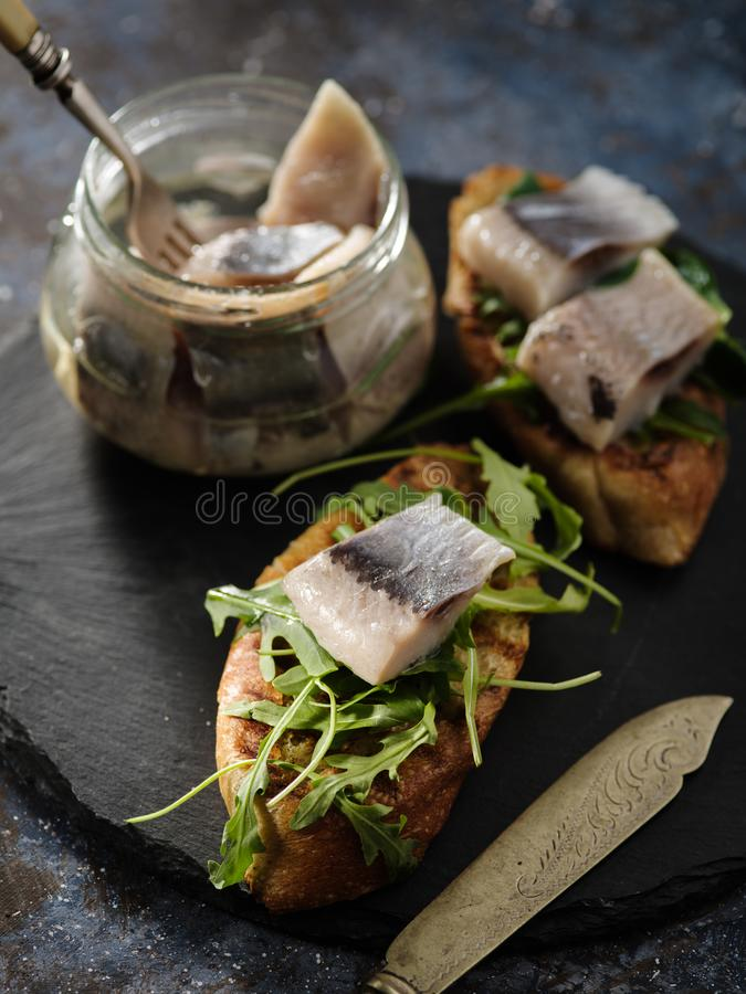 Smorrebrod danese tradizionale del panino dell'aringa sul verro di taglio fotografia stock