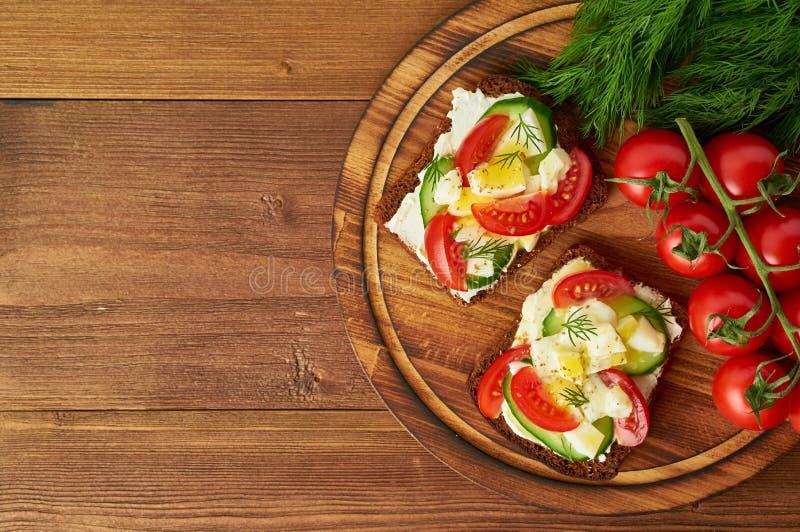 Smorrebrod - panini danesi tradizionali Pane di segale nero con l'uovo sodo, formaggio cremoso, cetriolo, pomodori su di legno ma fotografie stock libere da diritti
