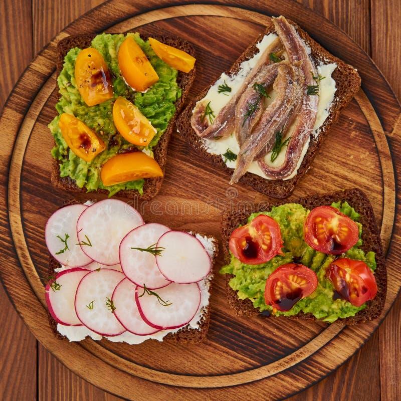 Smorrebrod - traditionele Deense sandwiches Zwart roggebrood met vissen, ansjovissen, avocado, tomaten, radijs op donkere bruine  royalty-vrije stock fotografie