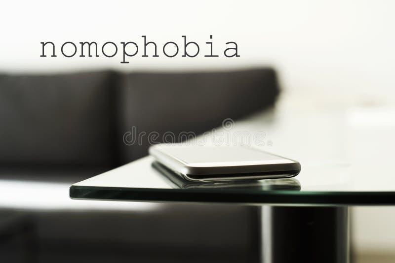 Smpartphone sur un nomophobia en verre de table et de textes photos libres de droits