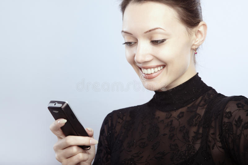 SMS. Smiling lady reading or sending SMS stock photo