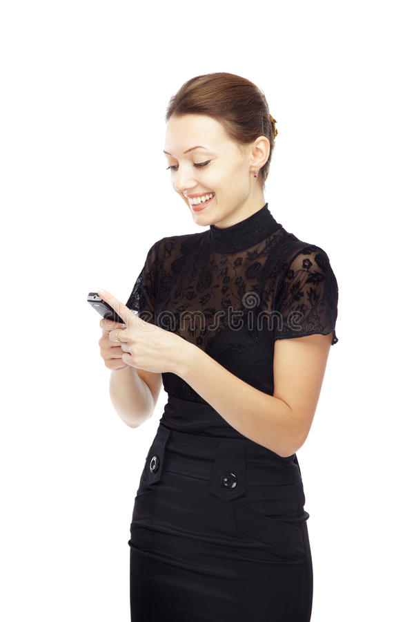 SMS. Smiling lady on a white background sending or receiving SMS via cell phone royalty free stock photo