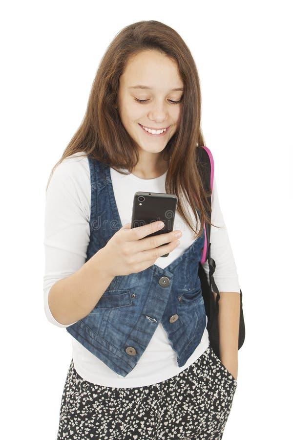 Sms adoráveis da leitura da estudante em seu telefone celular foto de stock