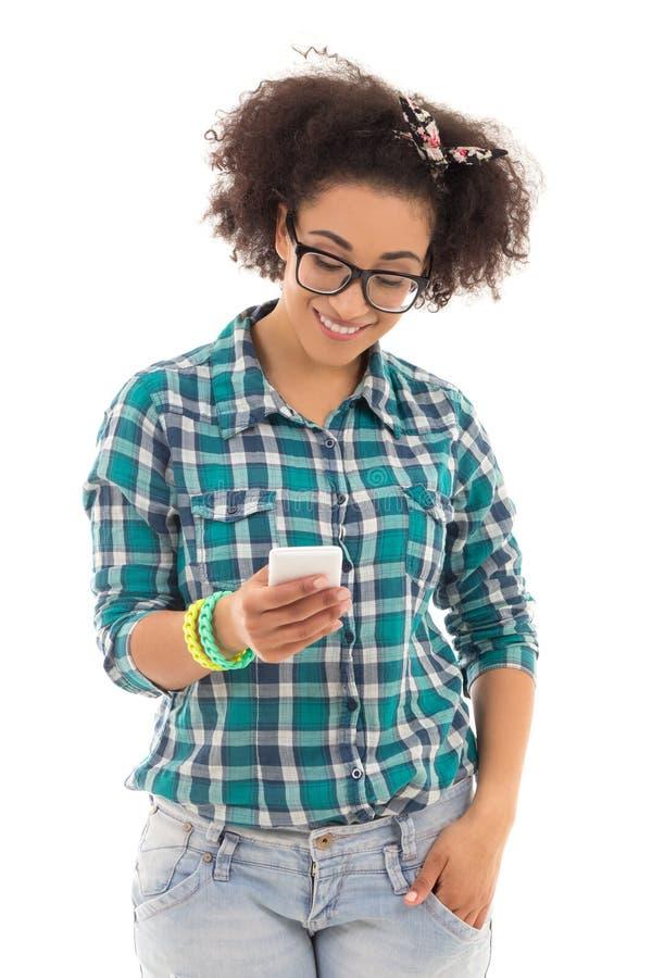 Sms begrepp - tonårs- flicka för härlig afrikansk amerikan med mobil royaltyfri foto