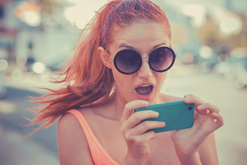 SMS. Closeup portrait funny shocked anxious scared young girl looking at phone seeing shocking news photos message with disgusting royalty free stock images