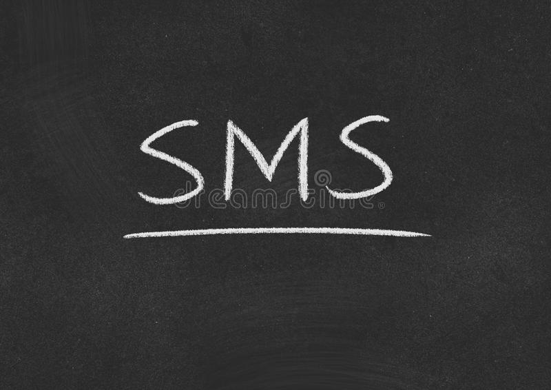 Sms. Concept word on a blackboard background royalty free stock photo