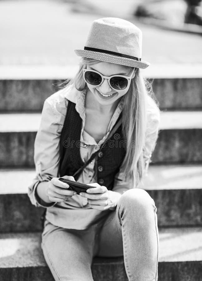 Sms d'écriture de fille de hippie tout en se reposant sur des escaliers image libre de droits