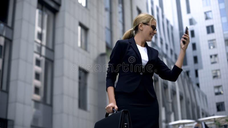 Sms de júbilo da mulher de negócios feliz com as boas notícias, fazendo o investimento rentável fotografia de stock royalty free