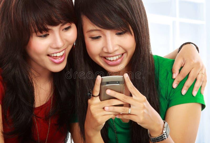 Sms de sorriso da leitura da mulher asiática nova foto de stock royalty free