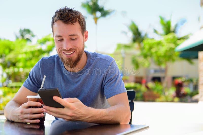 SMS del hombre de Smartphone que manda un SMS al café de consumición en el café foto de archivo libre de regalías