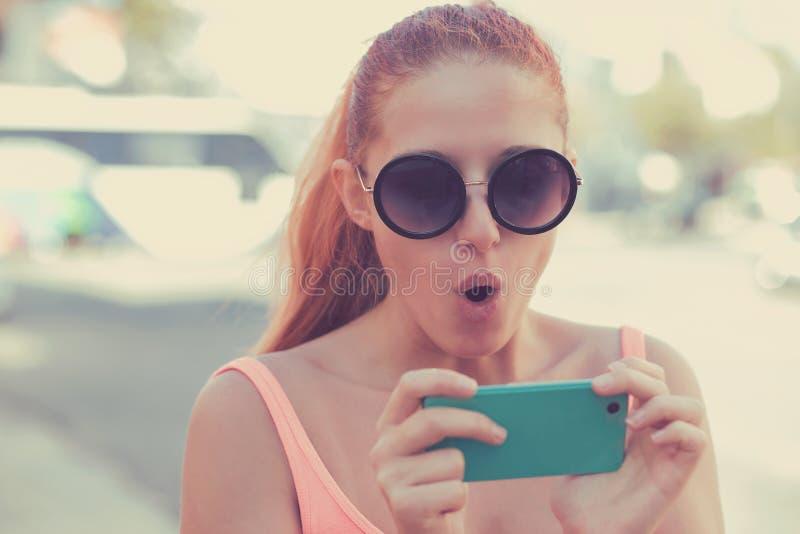 SMS Moça assustado ansiosa chocada engraçada do retrato do close up que olha o telefone que vê a mensagem das fotos das más notíc imagem de stock royalty free