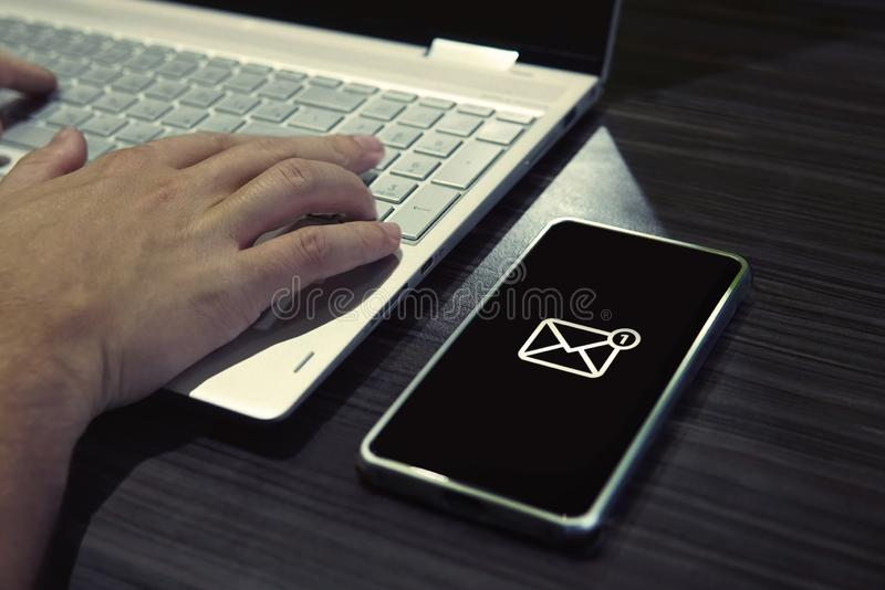 SMS password for network access on phone while typing on laptop. Generic icon of mail on black-screened smartphone lying on the royalty free stock photography
