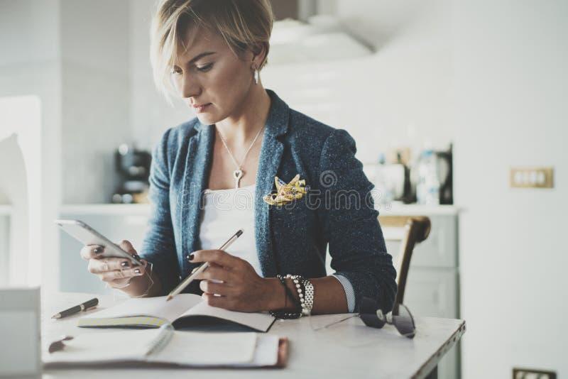 SMS que manda un SMS de la empresaria atractiva con el socio vía el teléfono moderno mientras que escribe una cierta información  foto de archivo