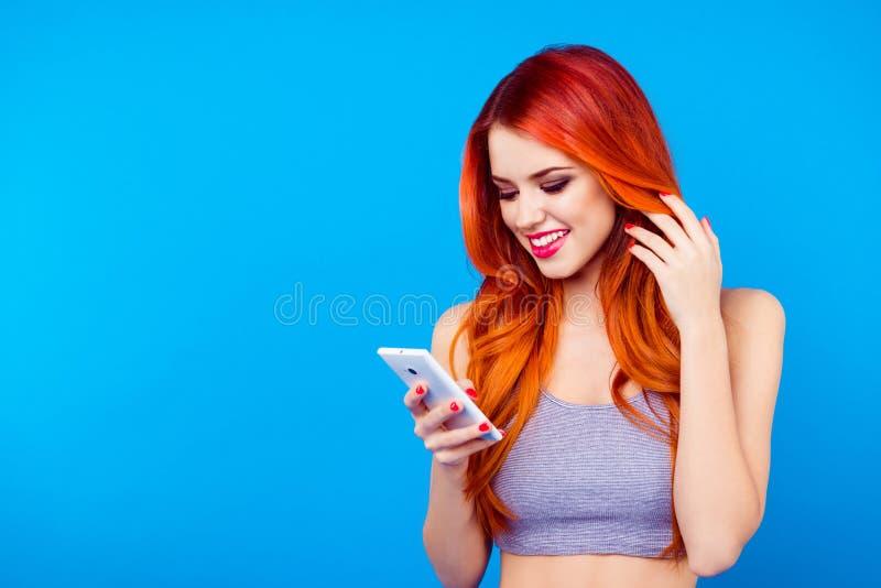 SMS que mecanografía de la muchacha bastante delgada en el teléfono móvil Ciérrese encima del retrato de encantar la transferenci imagen de archivo