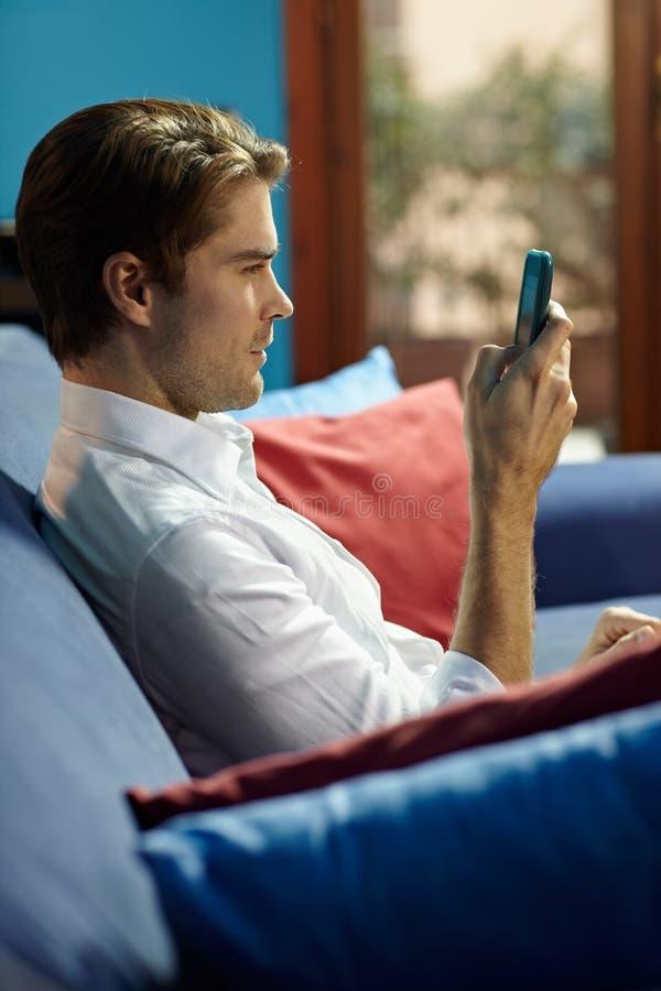 Sms que pulsan del hombre en el teléfono celular imagen de archivo libre de regalías