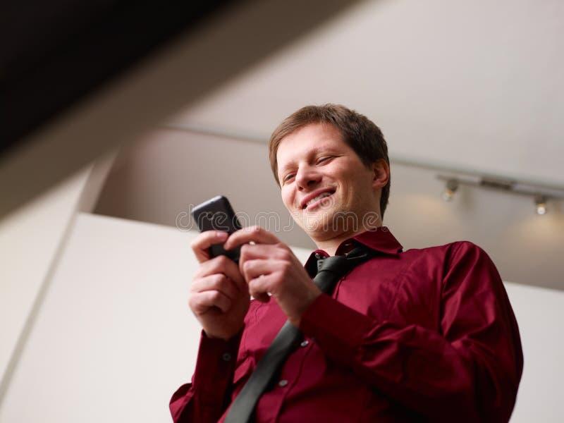 Sms que pulsan del hombre en smartphone y la sonrisa imagen de archivo