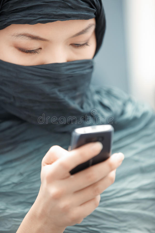 SMS sending. Oriental lady in hijab sending SMS via cell phone stock image