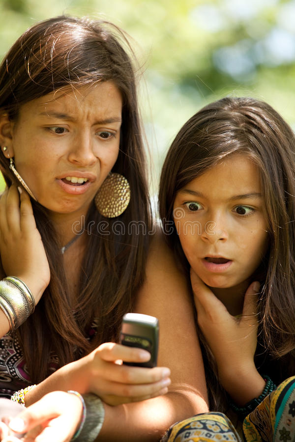 Sms surprise. Two young sisters reading a new sms at the cellular stock image